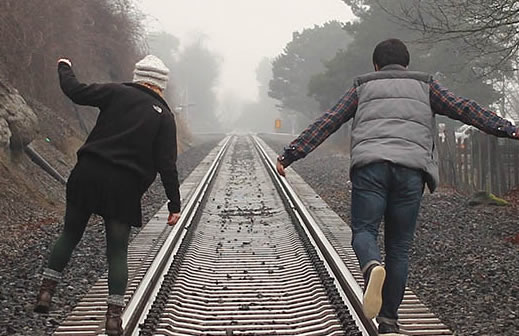 A couple walking on a RR track.